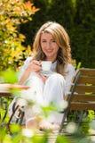 Het drinken van de vrouw koffie bij ontbijt in de tuin Royalty-vrije Stock Afbeeldingen