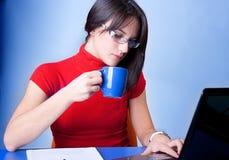 Het drinken van de vrouw koffie en het doen van het werk Stock Afbeeldingen