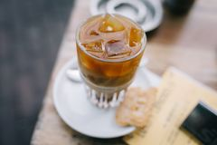 Het drinken van een bevroren koffie in de zomer met latte op een houten lijst stock fotografie