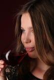 Het drinken van het meisje alcohol Sluit omhoog Donkerrode achtergrond Stock Afbeelding