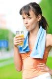 Het drinken van het meisje sap na oefening stock fotografie
