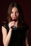 Het drinken van het meisje wijn Sluit omhoog Donkerrode achtergrond Royalty-vrije Stock Afbeelding