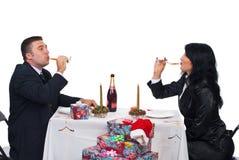 Het drinken van het paar champagne bij de lijst van Kerstmis Stock Foto