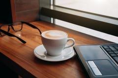 Het drinken van koffie terwijl het gebruiken van laptop in koffie Kop van koffie met glazen en laptop in doopvont van het venster Royalty-vrije Stock Foto