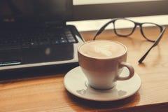 Het drinken van koffie terwijl het gebruiken van laptop in koffie Kop van koffie met glazen en laptop in doopvont van het venster Stock Afbeelding