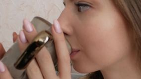 Het drinken van het meisje van een kop stock videobeelden