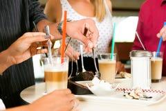 Het drinken van vrienden melkkoffie en het eten van cake royalty-vrije stock foto's