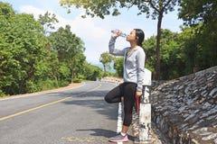 Het drinkwater van de atletenvrouw van een fles na jogging Stock Afbeelding