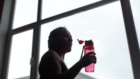 Het drinkwater van de atletenvrouw van fles in langzame motie in de gymnastiek stock videobeelden
