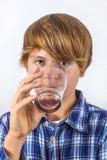 Het drinkwater van de jongen uit een glas Stock Afbeeldingen