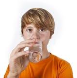 Het drinkwater van de jongen uit een glas Stock Afbeelding