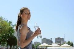 Het drinkwater van de sportvrouw en luister aan muziek royalty-vrije stock foto