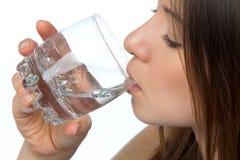 Het drinkwater van de vrouw van glas Stock Foto's
