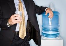Het drinkwater van de zakenman van waterkoeler royalty-vrije stock fotografie