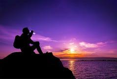Het drinkwater van het jonge mensensilhouet op de steen bij zonsondergang stock fotografie