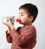 Het drinkwater van het kind dat op grijs wordt geïsoleerds stock foto's