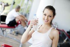 Het drinkwater van het meisje in de gymnastiek Stock Foto's