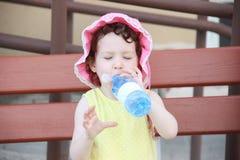 Het drinkwater van het meisjeskind met genoegen uit plastic fles op de bank stock afbeeldingen