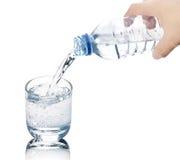 Het drinkwater wordt gegoten van een fles in een glas Stock Foto