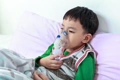 Het droevige Aziatische kind houdt een inhaleertoestel van de maskerdamp voor behandeling van asth stock fotografie