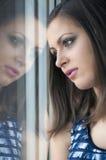Het droevige jonge meisje letten op door het venster Stock Afbeelding