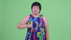 Het droevige jonge te zware Aziatische vrouw geven beduimelt neer stock video
