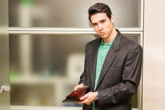 Het droevige kijken jonge mens die lege portefeuille tonen stock afbeelding
