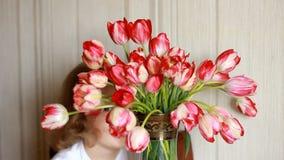Het droevige kind is beledigd en huiden achter een boeket van tulpen De baby drukt inbreuk uit stock videobeelden