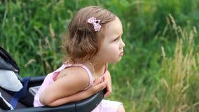 Het droevige kind zit in een wandelwagen en wacht op haar moeder Niet bevallen en beledigd jong geitje stock videobeelden