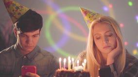 Het droevige meisje en een mens die in verjaardagshoeden voor cake met kaarsen zitten die op hun cellphones texting Verslaving aa stock video