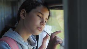 Het droevige meisje kijkt uit het treinvenster De levensstijl van het de spoorwegconcept van het reisvervoer Het tienermeisje mis stock video