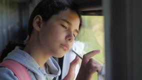 Het droevige meisje kijkt uit het treinvenster de spoorwegconcept van het reisvervoer het meisje van de levensstijltiener mist re stock footage