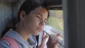 Het droevige meisje kijkt uit het treinvenster de spoorwegconcept van het reisvervoer het meisje van de tienerlevensstijl mist re stock footage