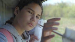 Het droevige meisje kijkt uit het treinvenster De spoorwegconcept van het reisvervoer Het tienermeisje mist aan de gang reizend stock video