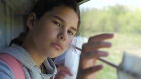 Het droevige meisje kijkt uit het treinvenster de spoorwegconcept van het reisvervoer het tienermeisje mist aan de gang reizend stock videobeelden