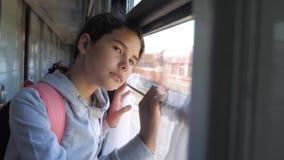 Het droevige meisje kijkt uit het treinvenster De spoorwegconcept van het reisvervoer Het tienermeisje mist reizend in een trein stock video