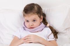 Het droevige meisje ligt in een wit bed royalty-vrije stock fotografie