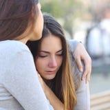 Het droevige meisje schreeuwen en een vriend die haar troosten Stock Foto's