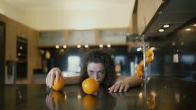 Het droevige meisje spelen met sinaasappelen op lijst stock videobeelden