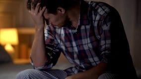 Het droevige mens schreeuwen, die op bed, relatief verlies, gebrek aan steun, zorg en verdriet zitten royalty-vrije stock afbeelding