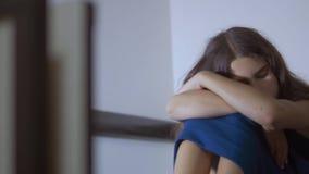Het droevige verstoorde meisje omhelst geweld haar voeten is gedeprimeerde en zelfmoord weinig betreurenswaardige droefheidsjuffr stock footage