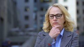 Het droevige vrouwelijke bedrijfarbeider denken aan het werk, ongerust gemaakte bedrijfsdame, pensioenleeftijd stock videobeelden