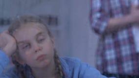 Het droevige weesmeisje die regen, paar bekijken die, bevordert familie komst zich erachter bevinden stock videobeelden