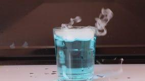 Het droge ijs in een glas blauw water en veroorzaakt witte rook op witte vloer met zwarte achtergrond stock videobeelden