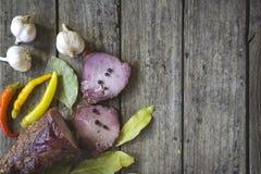 Het droge varkensvleesvlees met Spaanse peperspeper, knoflook en laurierblad op houten lijst Royalty-vrije Stock Afbeeldingen