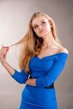 Het dromen van jong blonde meisje wat betreft haar Stock Afbeelding