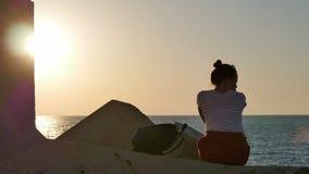 Het dromen van jonge vrouwenzitting op de rotsen dichtbij het overzees bij zonsondergang stock footage