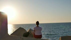 Het dromen van jonge vrouwenzitting op de rotsen die van overzees genieten bij zonsondergang stock video