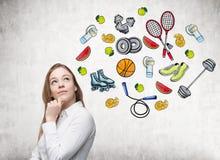 Het dromen van mooie dame denkt over haar keus van sportactiviteit De kleurrijke sportpictogrammen worden getrokken op de concret Royalty-vrije Stock Afbeelding