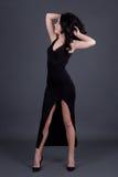 Het dromen van mooie vrouw in het lange zwarte kleding stellen over grijs Stock Afbeeldingen